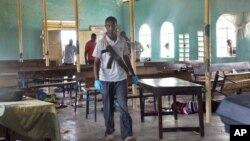 An armed Kenyan policeman walks inside the African Inland Church in Garissa, July 1, 2012.