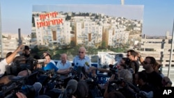 Israeli Minister of Housing and Construction Uri Ariel (C) speaks to journalists during a ceremony to mark the resumption of the construction of housing units in an east Jerusalem neighborhood, August 11, 2013.