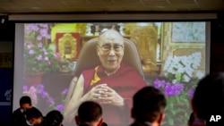 Pejabat pemerintah Tibet di pengasingan menonton penayangan pesan dari pemimpin spiritual mereka Dalai Lama (di layar) dalam upacara untuk menandai ulang tahun ke-86 pemimpin Tibet di Dharmsala, India, Selasa, 6 Juli 2021. (AP Photo/Ashwini Bhatia)