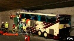 Regu penyelamat dan polisi memeriksa bus wisatawan di terowongan A9 dekat Sierre, dekat perbatasan Swis (14/3).