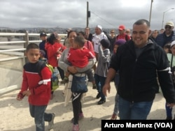 """Members of the Central American migrants caravan arrive at the """"El Chaparral"""" pedestrian crossing on their way to U.S. Customs and Border Patrol, at the U.S.-Mexico border in Tijuana, Mexico, April 29, 2018. (A. Martinez/VOA)"""