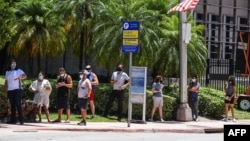 "People wait for their testing at a ""walk-in"" and ""drive-through"" coronavirus testing site in Miami Beach, Florida on June 24, 2020."