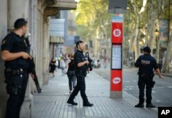 Armed police officers patrol a street in Las Ramblas, Barcelona, Spain, Aug. 18, 2017.