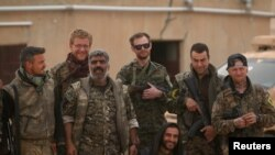 FILE - Syrian Democratic Forces (SDF) fighters pose with foreign volunteer fighters inside Tabqa military airport after taking control of it from Islamic State fighters, west of Raqqa city, Syria April 9, 2017.