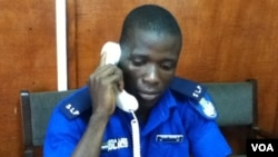 Sheka Conteh answers phones at the police call centre, Freetown, February 1, 2013. (N. de Vries/VOA)
