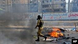 Seorang anggota pasukan keamanan Mesir tampak berjalan di dekat lokasi bentrokan dengan pendukung Morsi di Alexandria, Mesir Jumat (3/1).