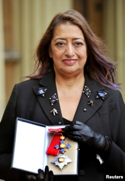 FILE - Architect Zaha Hadid poses for photographs with her Dame Commander of the Order of the British Empire (DBE) medal, after it was awarded to her by Britain's Princess Anne during an Investiture Ceremony at Buckingham Palace, in London, Nov. 7, 2012.