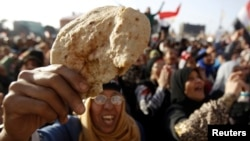 FILE - An Egyptian holds a piece of bread to protest against the high prices of goods in Tahrir Square in Cairo, February 8, 2013.