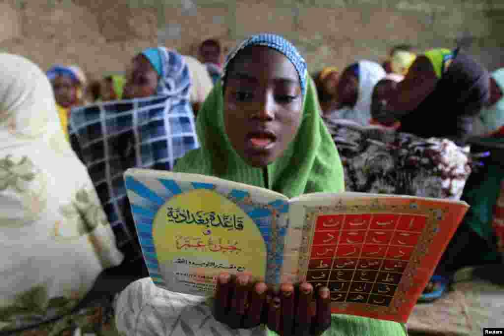 Nigeriyaning janubiy Kano shahrida joylashgan Qur'on maktabida yosh qiz Qur'on o'qimoqda. 21-iyul, 2012-yil.