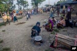 Seorang perempuan Muslim Rohingya, yang menyeberang dari Myanmar ke Bangladesh, memasak di pinggir jalan dekat kamp pengungsi Mushani, Bangladesh, Sabtu, 16 September 2017.