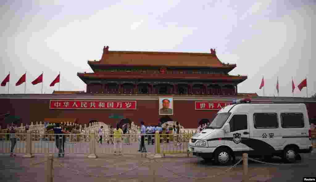 A police car is seen in front of a giant portrait of China's late Chairman Mao Zedong in Tiananmen Square in Beijing, June 4, 2014.