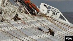 Dua orang anggota tim pertolongan Italia tengah bekerja di atas kapal Concordia (17/1). Upaya pertolongan dihentikan sementara, karena posisi kapal yang bergeser mempersulit upaya pencarian korban.