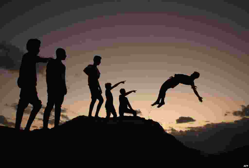 Palestinian youths practice parkour at sunset in Gaza City.