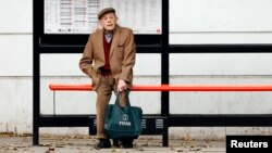 "FILE - A man sits by himself at a bus stop in London, Oct. 18, 2013. Health Secretary Jeremy Hunt said at the time that there were hundreds of thousands of people in England who were chronically lonely. A ""minister of loneliness"" has now been appointed to combat social isolation."