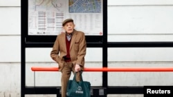 "FILE - A man sits by himself at a bus stop in London, Oct. 18, 2013. Health Secretary Jeremy Hunt said at the time that there were hundreds of thousands of people in England who were chronically lonely. A ""minister of loneliness has now been appointed to"