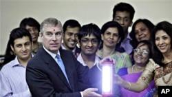 英国的安德鲁王子(左二)访问孟买一所大学时与学生和教师合影,他手里拿的是太阳能灯