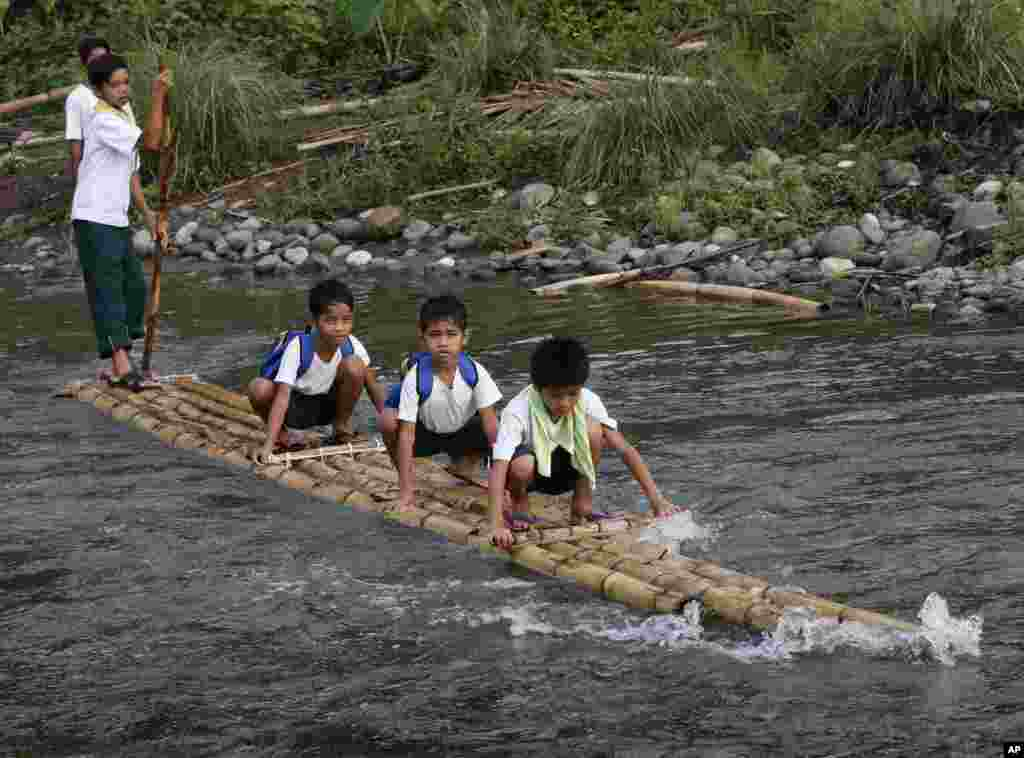 Elementary pupils cross a river on a raft to attend the opening of classes for the school year 2013-2014, at a remote village in Rodriguez township, Rizal province, about 50 kilometers (33 miles) east of Manila, Philippines.