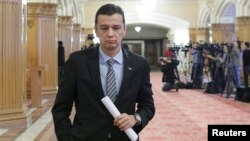 FILE - Romania's Prime Minister Sorin Grindeanu leaves a meeting at the parliament in Bucharest, Feb. 6, 2017.