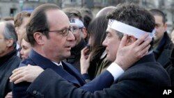 French President Francois Hollande comforts French columnist for Charlie Hebdo Patrick Pelloux as they take part with family members and relatives in a solidarity march in the streets of Paris, Jan. 11, 2015.
