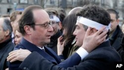French President Francois Hollande comforts French columnist for Charlie Hebdo Patrick Pelloux in a solidarity march in the streets of Paris, Jan. 11, 2015.