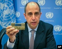 FILE - Tomas Ojea Quintana, the U.N. special investigator on human rights in North Korea, holds up a lock given to him by North Koreans who escaped from the country, during a press conference, Oct. 23, 2018, at U.N. headquarters in New York.