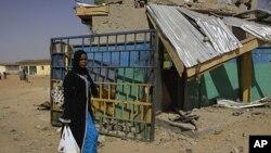 Uma mulher percorre as ruínas dos ataques coordenados de 20 de Janeiro da Boko contra as estações de polícia e edifícios governamentais no norte da Nigéria