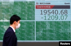 A passerby wearing a protective face mask following an outbreak of the coronavirus disease (COVID-19), walks past an electronic display showing Asian markets indices outside a brokerage in Tokyo, Japan, March 9, 2020.