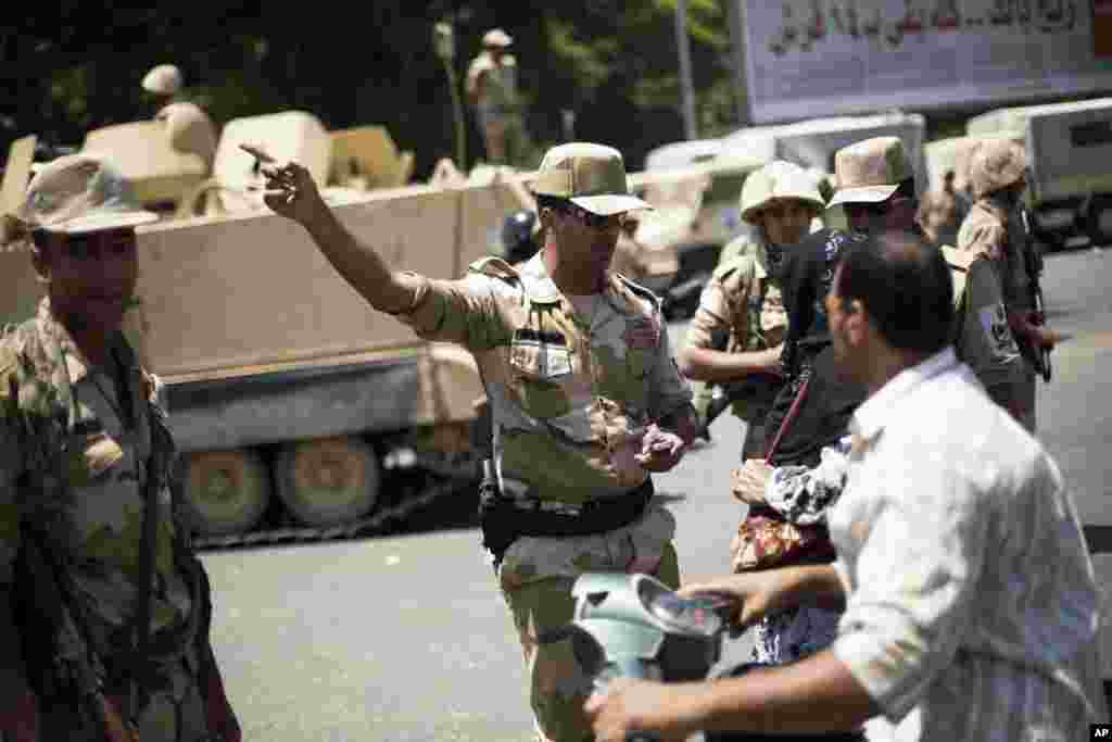 An Egyptian Army commander talks to citizens while securing the area near Cairo University, where Muslim Brotherhood supporters have gathered to support ousted president Mohammed Morsi in Cairo, July 4, 2013.