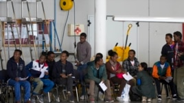 Eritrean refugees wait in a hanger to depart to Sweden.  The EU hopes to reduce the number of Eritrean migrants and refugees through aid programs aimed at stabilizing the country.