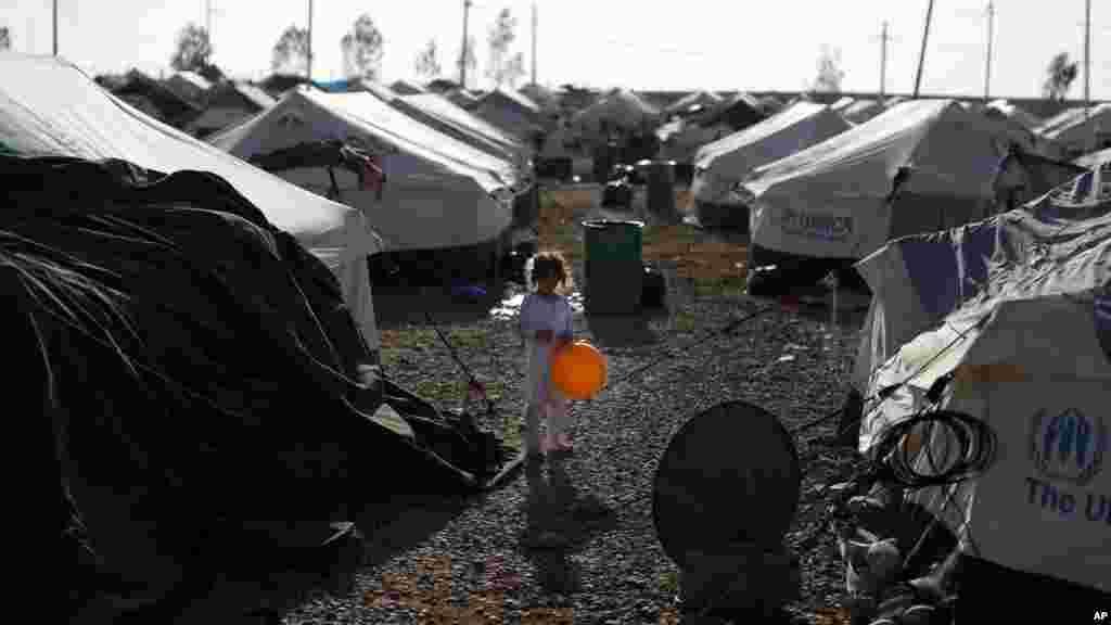 در اردوگاه آوارگان سازمان ملل، کودکی با بادکنکش بازی میکند. بر اساس برآوردها، از زمان حمله شورشیان داعش در خردادماه تا کنون، ۱.۵ میلیون نفر در داخل عراق آواره شده اند - اربیل، ۹ شهریور