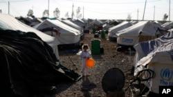 ເດັກນ້ອຍຄົນນຶ່ງ ຖືໝາກປູມເປົ້າ ຢູ່ໃນຄ້າຍອົບພະຍົບແຫ່ງນຶ່ງ ໃນເມືອງ Irbil, 350 ຫຼັກ ຫ່າງຈາກແບກແດດໄປທາງທິດເໜືອ, ວັນທີ 30 ສິງຫາ 2014.