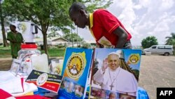 FILE - A vendor arranges portraits of Pope Francis outside of the Lubaga Cathedral in Kampala, Uganda, Nov. 13, 2015.