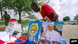 FILE - A vendor arranges portraits of Pope Francis outside of the Lubaga Cathedral in Kampala, Uganda, Nov. 13, 2015.