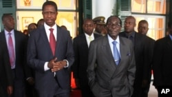 FILE - Zambian President Edgar Lungu (L) and Zimbabwean President Robert Mugabe are seen walking after a meeting at State House in Harare, Zimbabwe, Feb. 6, 2015.