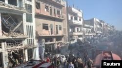 នៅក្នុងរូបថតផ្តល់ដោយបណ្តាញផ្សាយព័ត៌មានរដ្ឋស៊ីរី បង្ហាញពីកងទាហានស៊ីរីនិងប្រជាជនពិនិត្យកន្លែងផ្ទុះនៃគ្រាប់បែកអត្តឃាតពីរកន្លែងក្នុងទីក្រុង Homs នៅថ្ងៃទី២៨ ខែធ្នូ ឆ្នាំ២០១៥។
