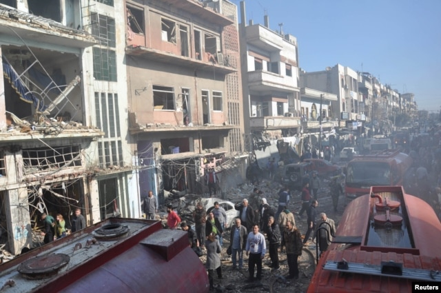 FILE - Syrian army soldiers and civilians inspect the site of two bombings in the Syrian city of Homs, in this photo provided by the state-owned Syrian Arab News Agency (SANA), Dec. 28, 2015.