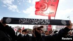 2013年1月14日突尼斯革命兩週年﹐一名薩拉菲派穆斯林極端分子高舉標語