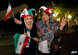 Iranian football supporters wearing the national football team's colors wave national flags outside Azadi stadium in Tehran, June 20, 2018, during a screening of the Russia 2018 World Cup Group B football match between Iran and Spain. Tehran's largest football stadium admitted thousands of women together with men for the first time since the Islamic Revolution of 1979.