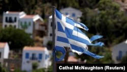 Bendera Yunani yang koyak terlihat di desa Meyisti di Pulau Kastellorizo, di bagian paling timur Yunani (4/7). (Reuters/Cathal McNaughton)