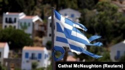 Türkiye kıyılarına 2 kilometre uzaklıktaki Meis adasında dalgalandırılan parçalanmış bir Yunan bayrağı