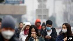 8일 짙은 스모그로 덮인 중국 베이징 거리의 시민들이 마스크를 하고 있다.