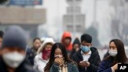 Warga Beijing berjalan dengan mengenakan masker untuk melindungi wajah dan penafasan mereka dari police saat berjalan kaki di kota tersebut, Selasa (8/12).
