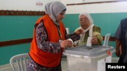A Palestinian woman casts her ballot at a polling station during municipal elections in the northern West Bank town of Anabta, near Tulkarm, May 13, 2017.