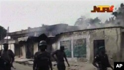 Sojoji su na wucewa ta jikin wasu gidajen da aka kona a Maiduguri, 8 Oktoba, 2012