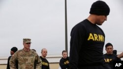 In this photo taken Tuesday, Jan. 8, 2019 Maj. Gen. Malcolm B. Frost, left, Commanding General for the U.S. Army Center for Initial Military Training, U.S. Army Training and Doctrine Command watches as troops participate in the new Army combat fitness tes