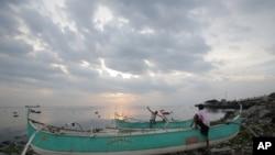 Nelayan Filipina tengah memeriksa perahu mereka yang mereka tambatkan di atas onggokan sampah di desa pantai Navotas, Manila Utara, Filipina (14/7). Warga Filipina tengah bersiap menghadapi badai tropis Rammasun, yang diperkirakan akan mencapai daratan di provinsi Catanduanes Selasa pagi (15/7).