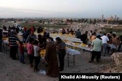 Orang-orang berkumpul untuk berbuka puasa selama bulan puasa Ramadhan, di Mosul, Irak, 15 April 2021. (Foto: REUTERS/Khalid Al-Mousily)