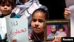 A Palestinian girl holds a photograph of her father, who is being held in a Palestinian prison, during a protest in the West Bank city of Ramallah, in support of prisoners who were allegedly arrested because of their affiliation with Hamas, May 14, 2013.