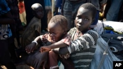 A newly-arrived displaced woman holds a child as they sit in the U.N. base in Bentiu, South Sudan, June 29, 2015.