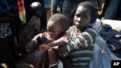 In this photo taken Monday, June 29, 2015, a displaced woman holds a child in the UN base in Bentiu, South Sudan. People seek shelter at UN camps across South Sudan to escape the country's violent civil conflict. (AP Photo/Jason Patinkin)